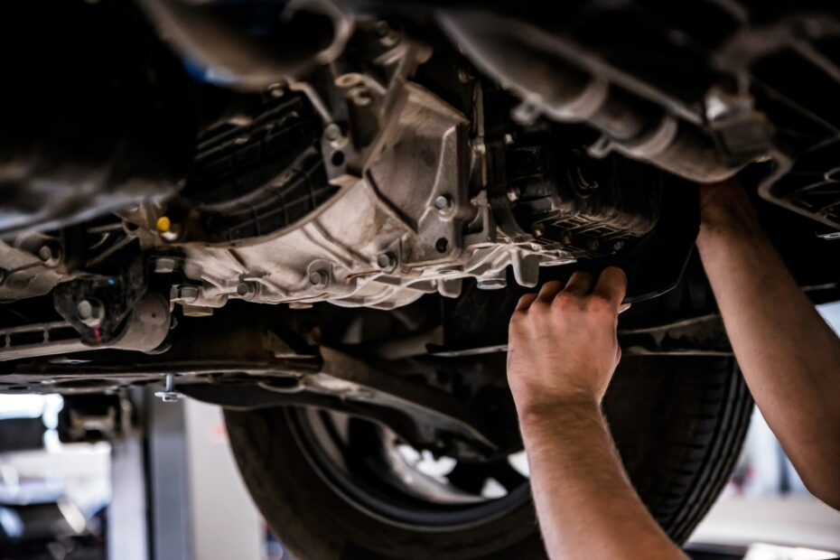 Close up of a mechanic hands repaires lifted car